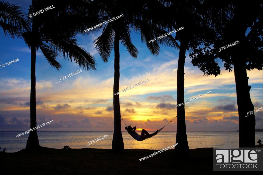 Stock Photo: Woman in hammock, and palm trees at sunset, Coral Coast, Viti Levu, Fiji, South Pacific.