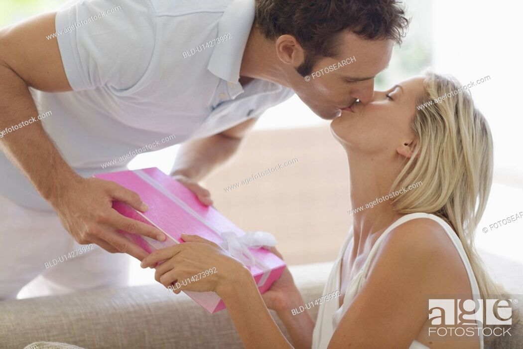 Stock Photo: Man giving present to woman and kissing on lips.