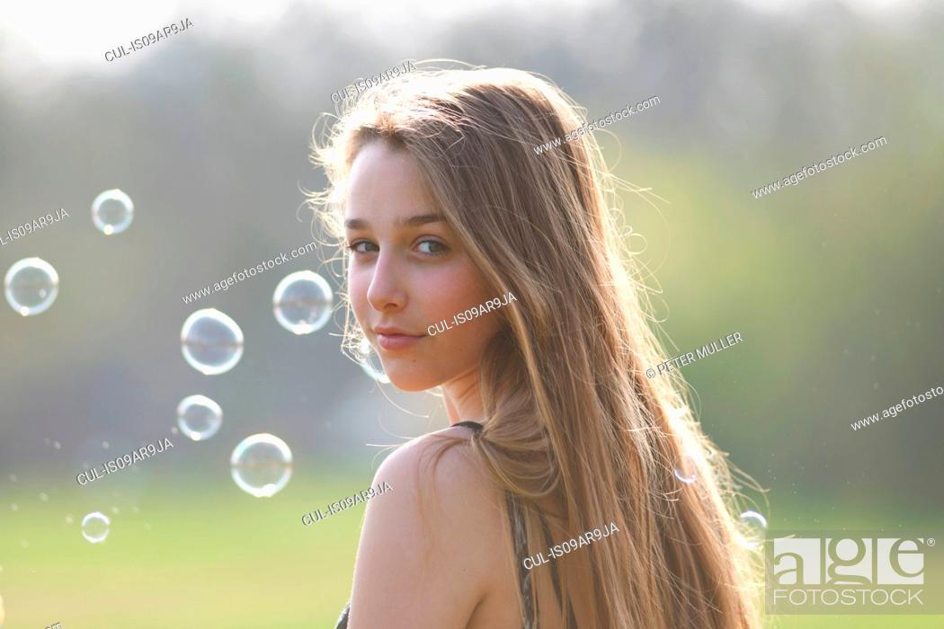 Stock Photo: Portrait of teenage girl looking over her shoulder in park.