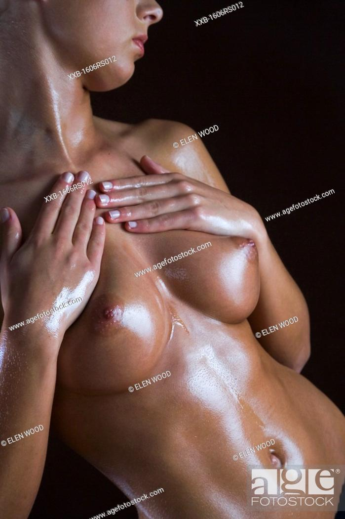 Stock Photo: young woman applying oil on breast.