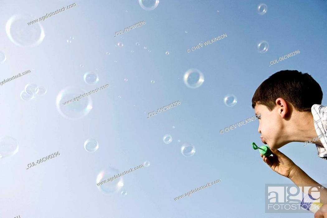 Stock Photo: Boy blowing bubbles.