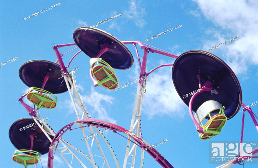 Stock Photo: Amusement park ride with empty cars, against blue sky with a bit of cloud.