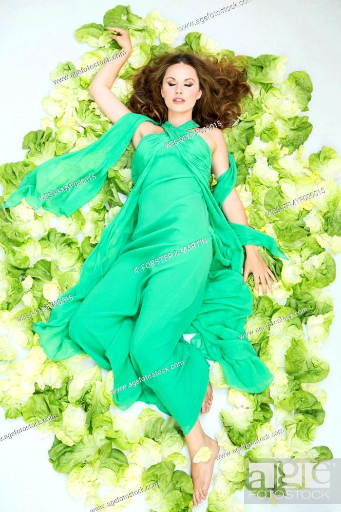 Stock Photo: Young woman lying on salad.