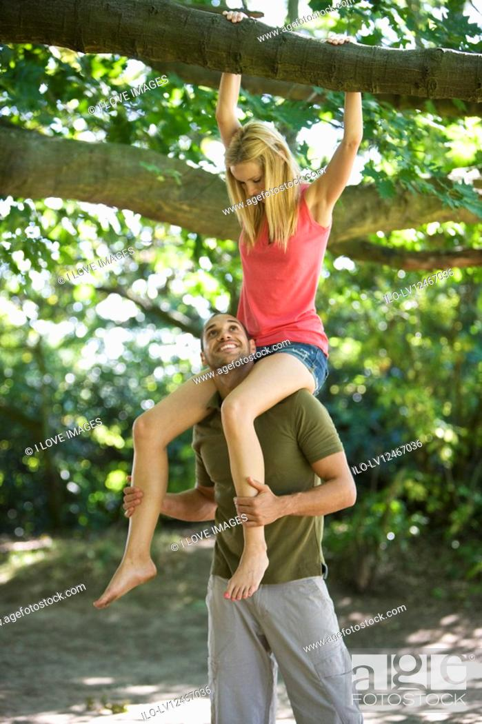 Stock Photo: A young man carrying his girlfriend on shoulders in the woods.