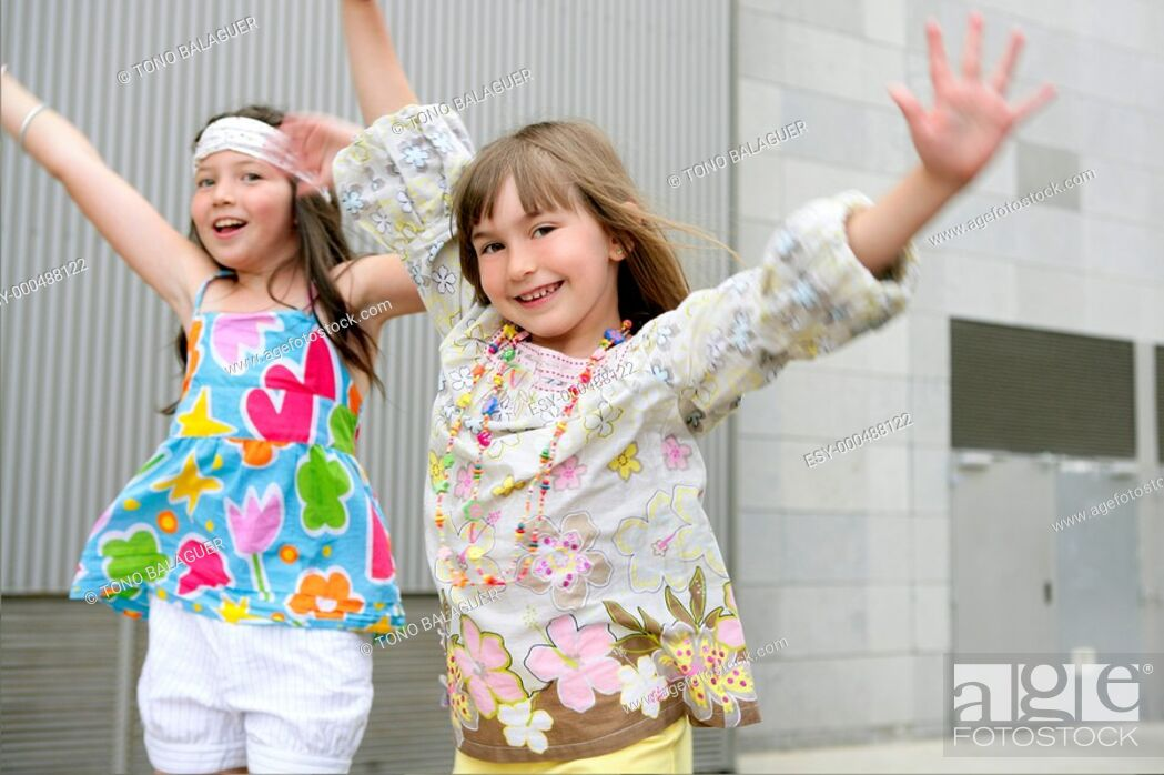 Stock Photo: Two little girls dancing in the city with gray building in background.