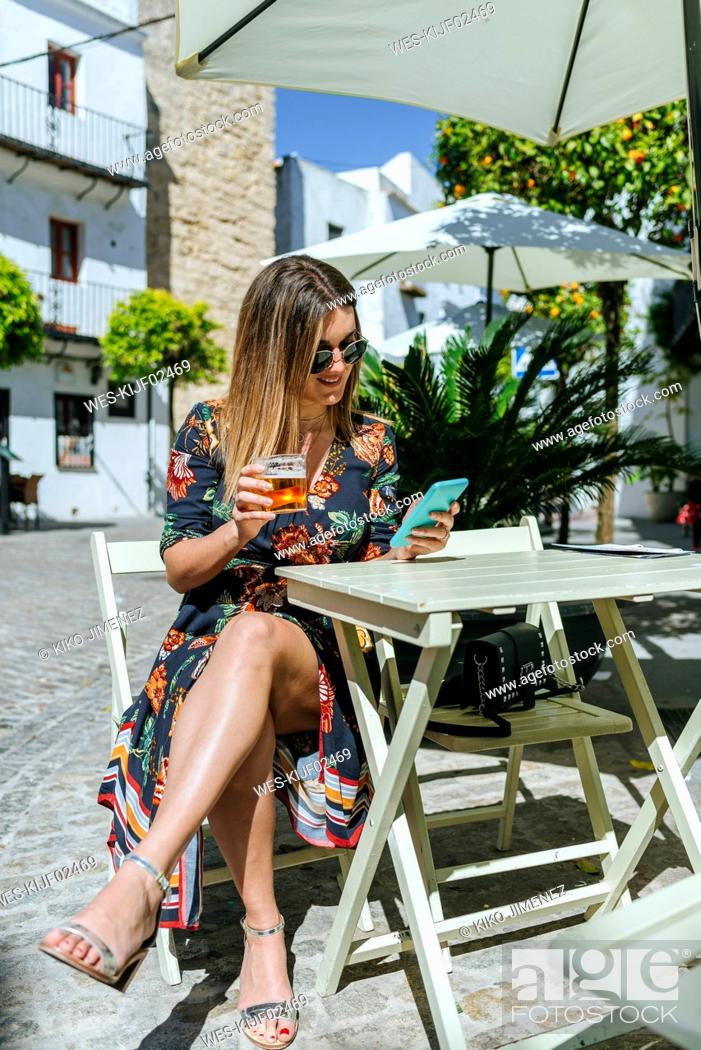 Stock Photo: Spain, Cadiz, Vejer de la Frontera, young woman sitting at street cafe with glass of beer looking at phone.
