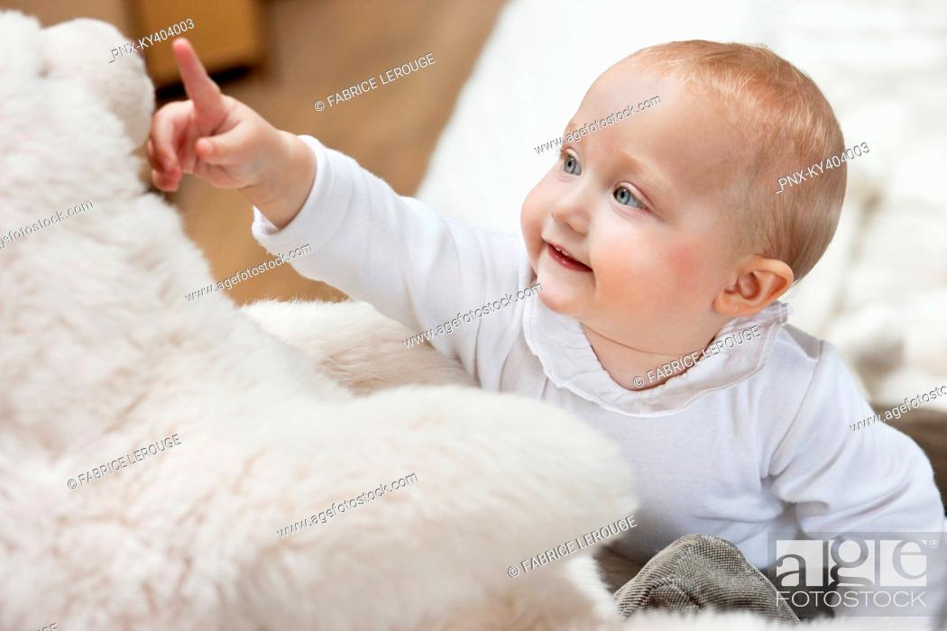 Stock Photo: Close-up of a baby girl playing with a teddy bear.