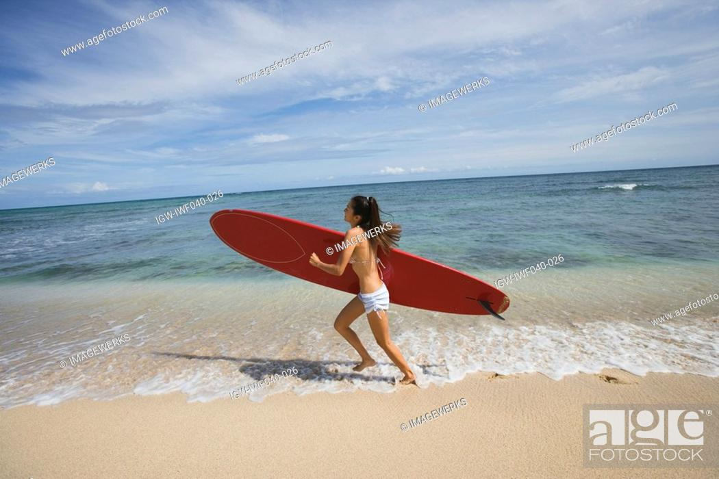 Stock Photo: View of a young woman running on beach.