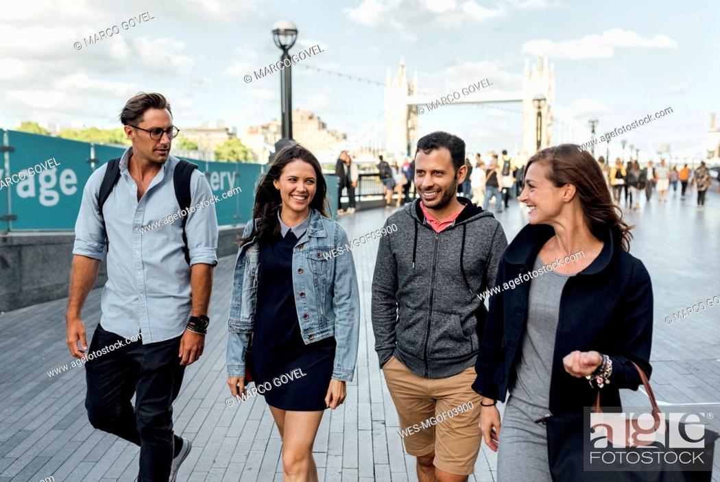Stock Photo: UK, London, happy friends walking near  Tower Bridge.