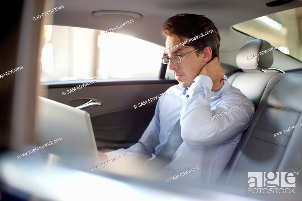 Stock Photo: Businessman using laptop in back seat of car.