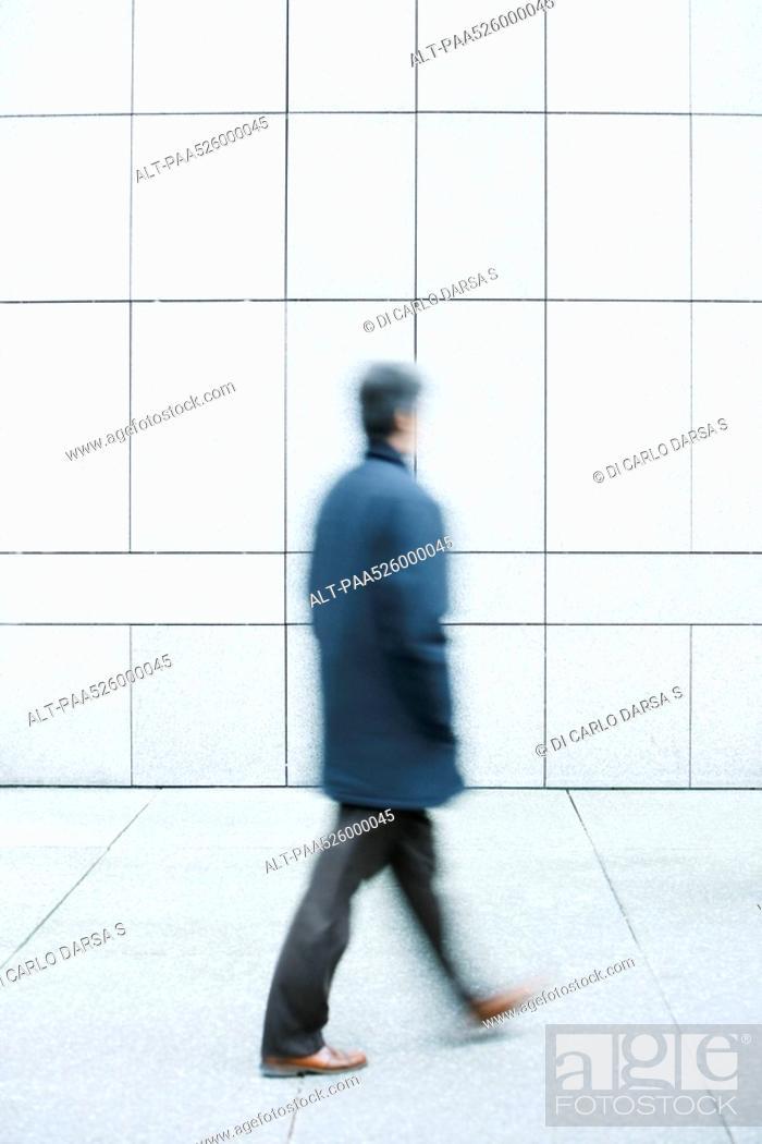 Stock Photo: Man walking with hands in pockets down sidewalk.