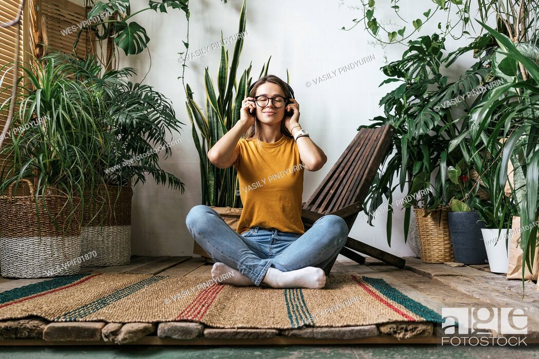 Stock Photo: Relaxed young woman sitting on the floor at home listening to music.
