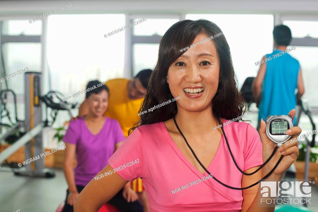 Stock Photo: Woman holding stopwatch on foreground, people working out in the gym on the background.