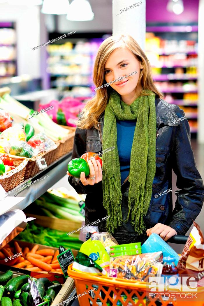 Stock Photo: Woman shopping for vegetables in a supermarket.