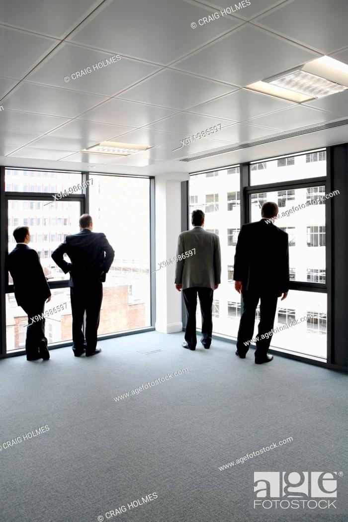 Stock Photo: Business men looking out of the windows at the view in a new office development.