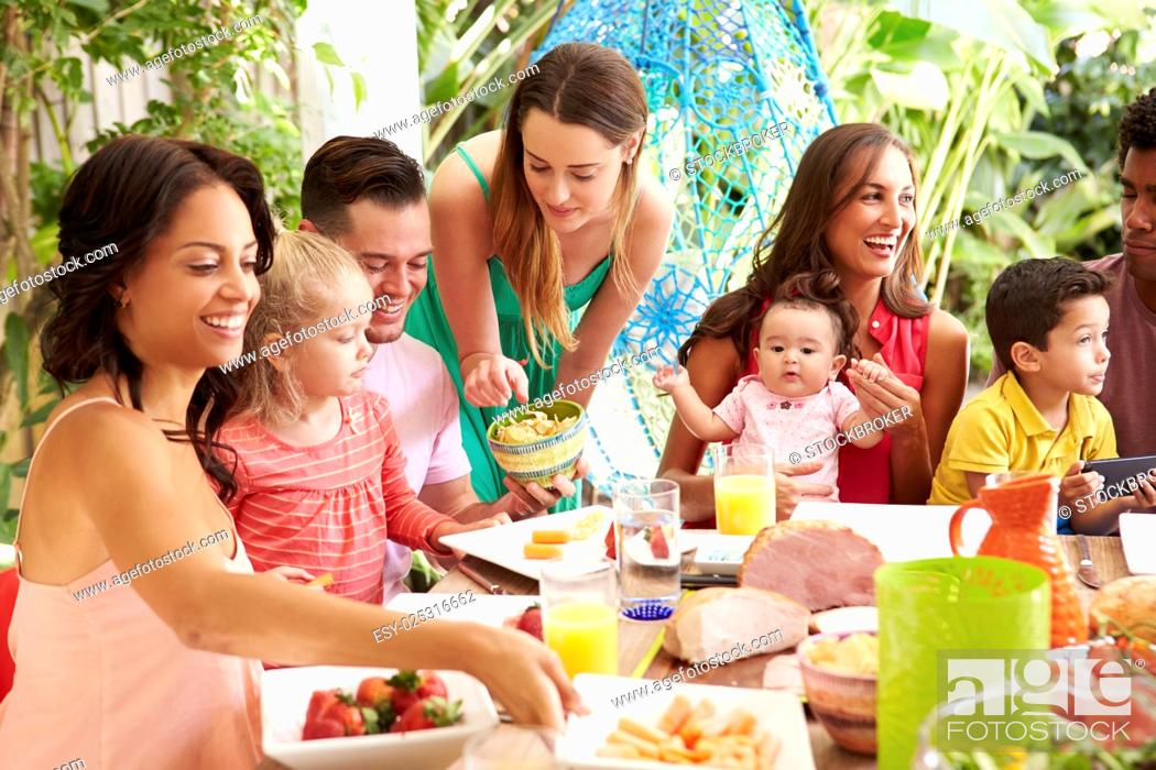 Stock Photo: Group Of Families Enjoying Outdoor Meal At Home.