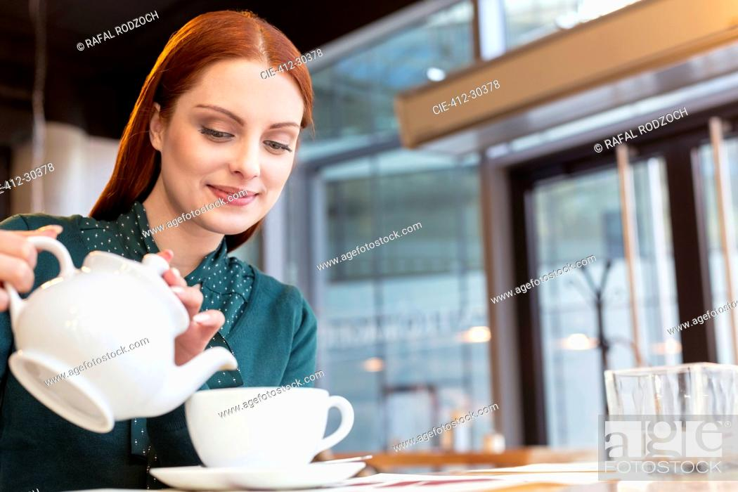 Stock Photo: Smiling woman pouring tea in cafe.