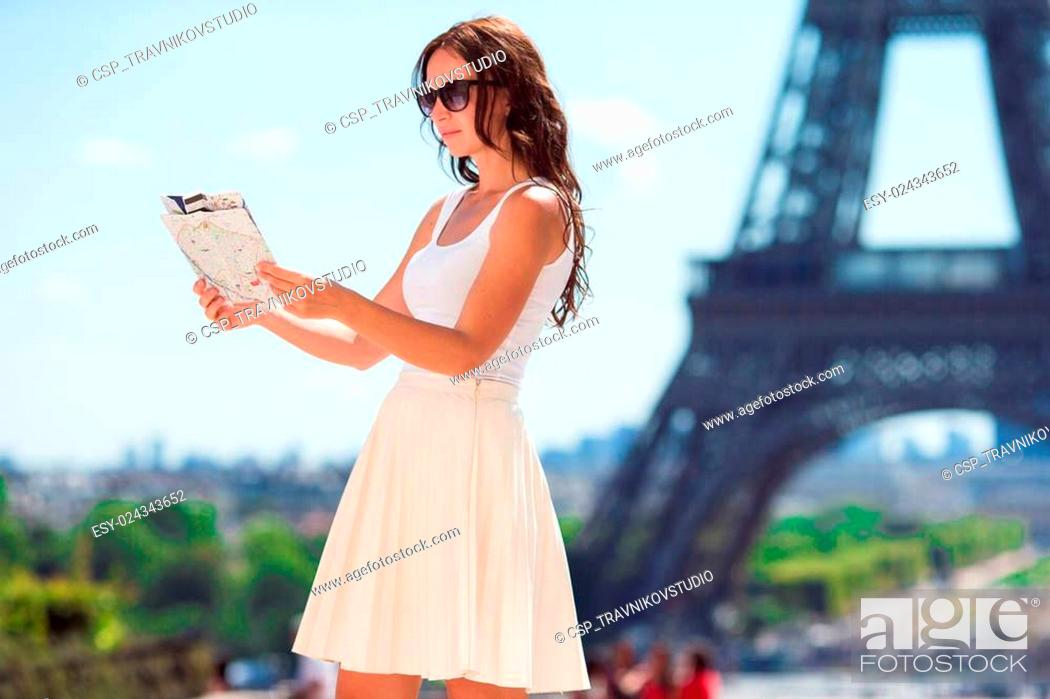 Stock Photo: Happy young woman with a city map in Paris background the Eiffel tower.