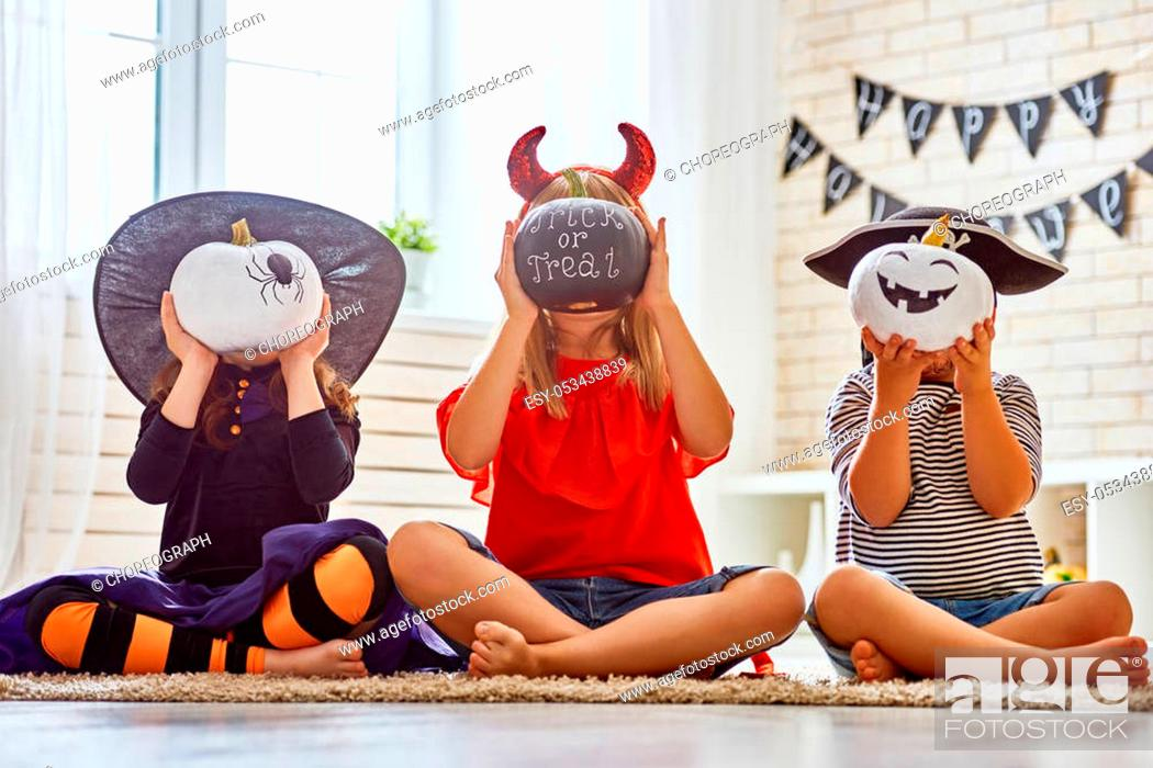 Stock Photo: Happy brother and two sisters on Halloween. Funny kids in carnival costumes indoors. Cheerful children play with pumpkins and candy.
