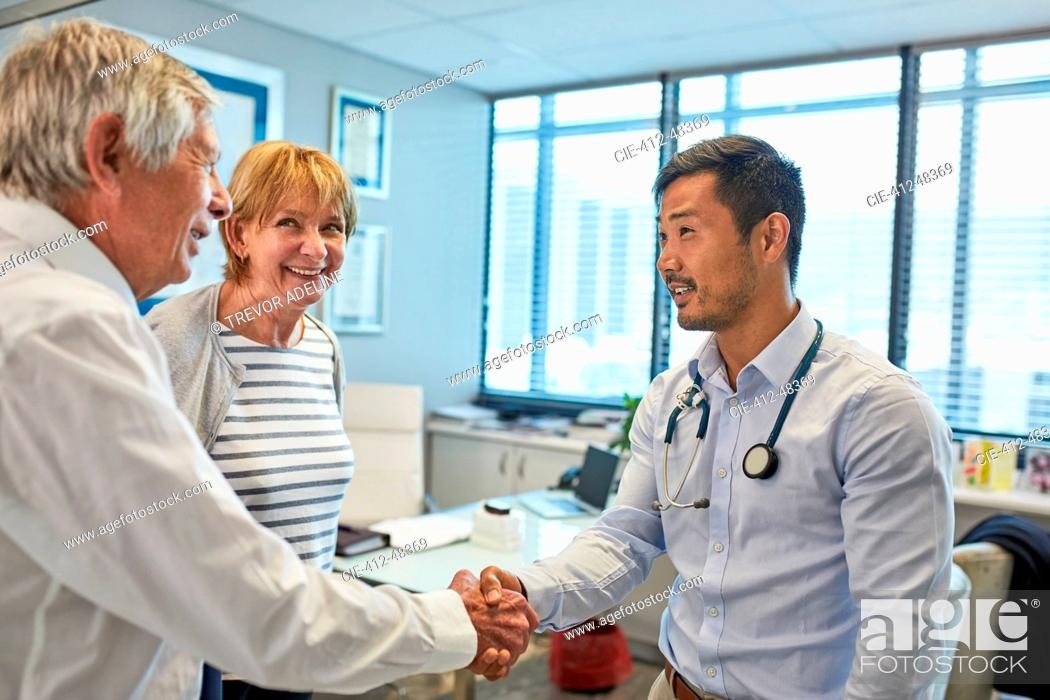 Stock Photo: Male doctor shaking hands with senior couple in clinic doctors office.