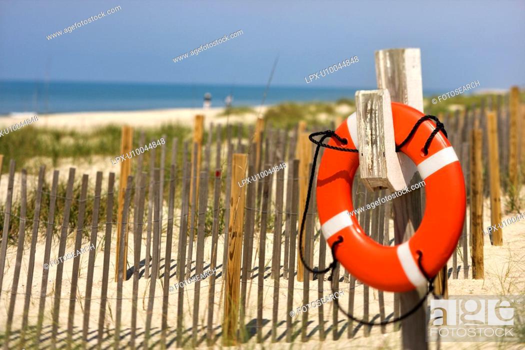 Stock Photo: Life preserver hanging on post on beach on Bald Head Island, North Carolina.
