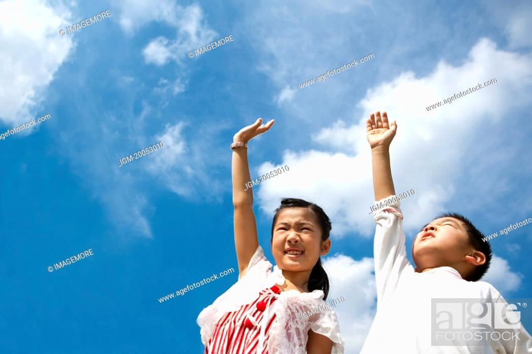 Stock Photo: A boy and a girl standing and reaching hands to sky.