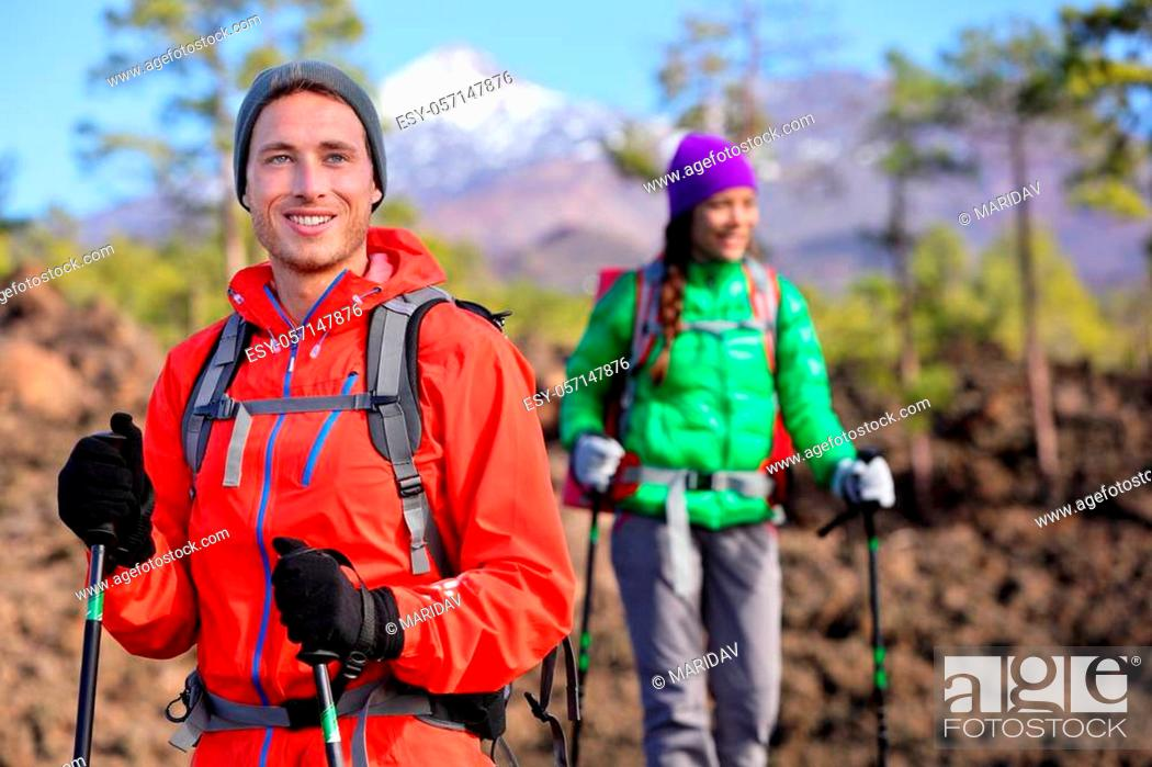 Imagen: Hiking hikers couple - healthy active lifestyle. Hiker couple hiking in beautiful mountain nature landscape. Woman and man hikers walking during hike on volcano.