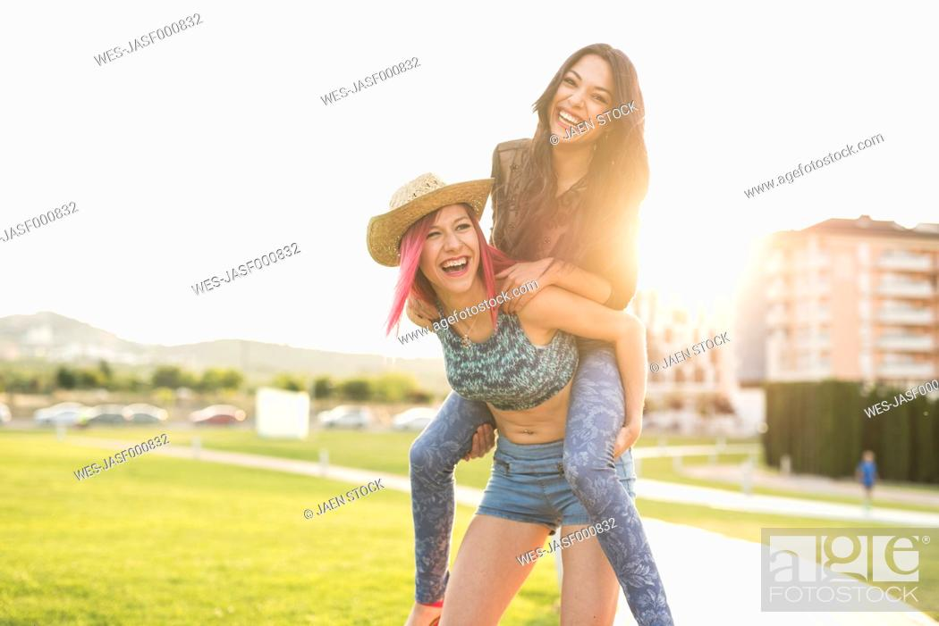 Stock Photo: Two girl friends playing piggy back in park.