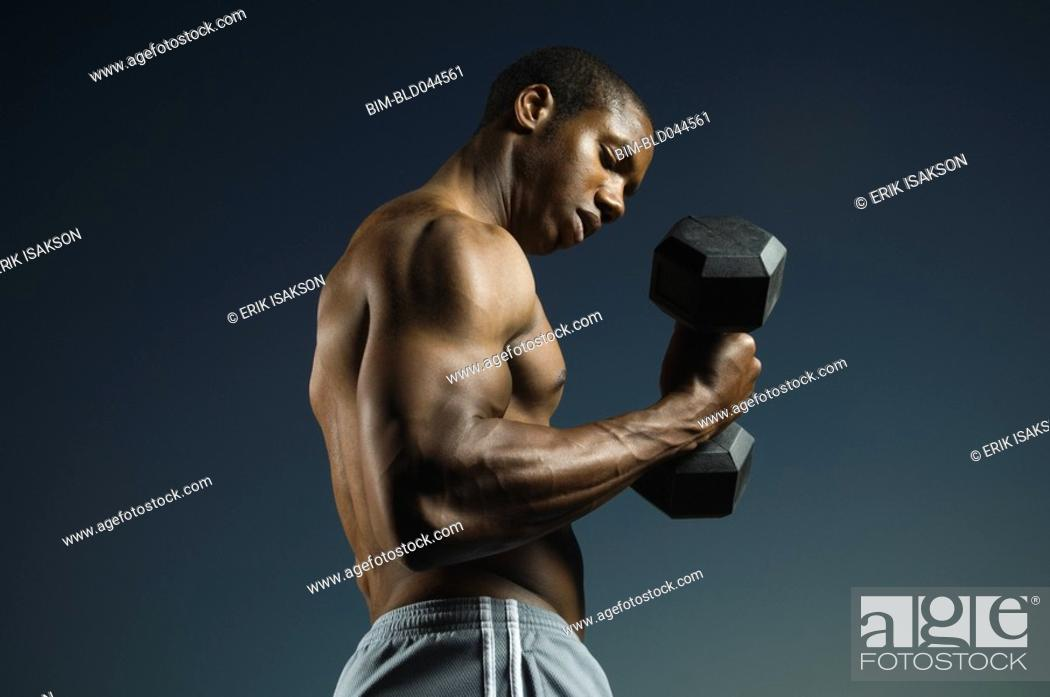 Stock Photo: African American man lifting weights.