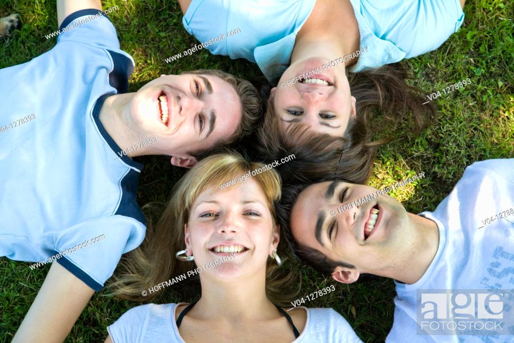 Imagen: Four young people smiling up at the camera, Germany, Europe.
