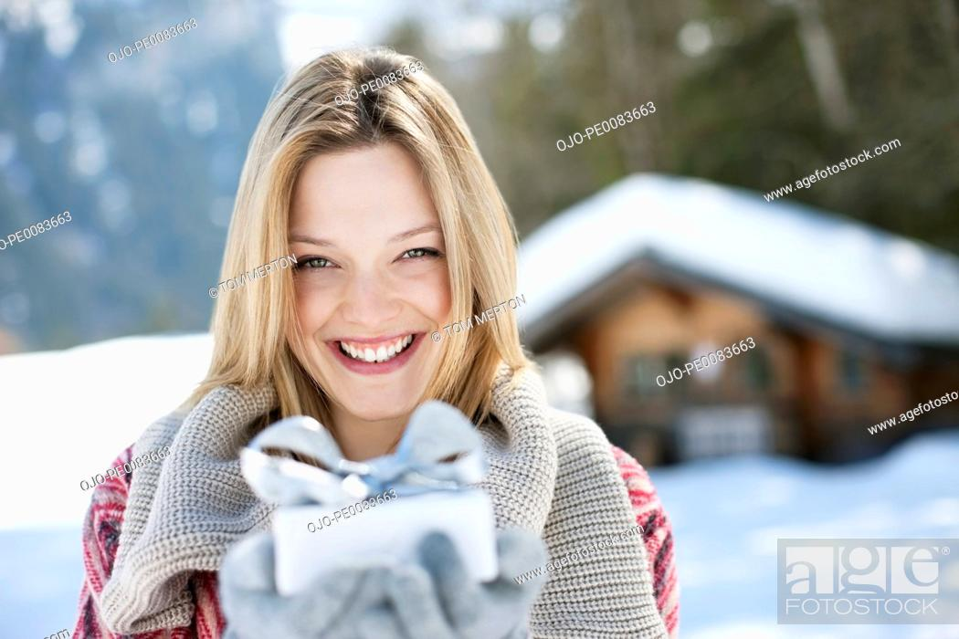 Stock Photo: Portrait of smiling woman holding Christmas gift in front of cabin.