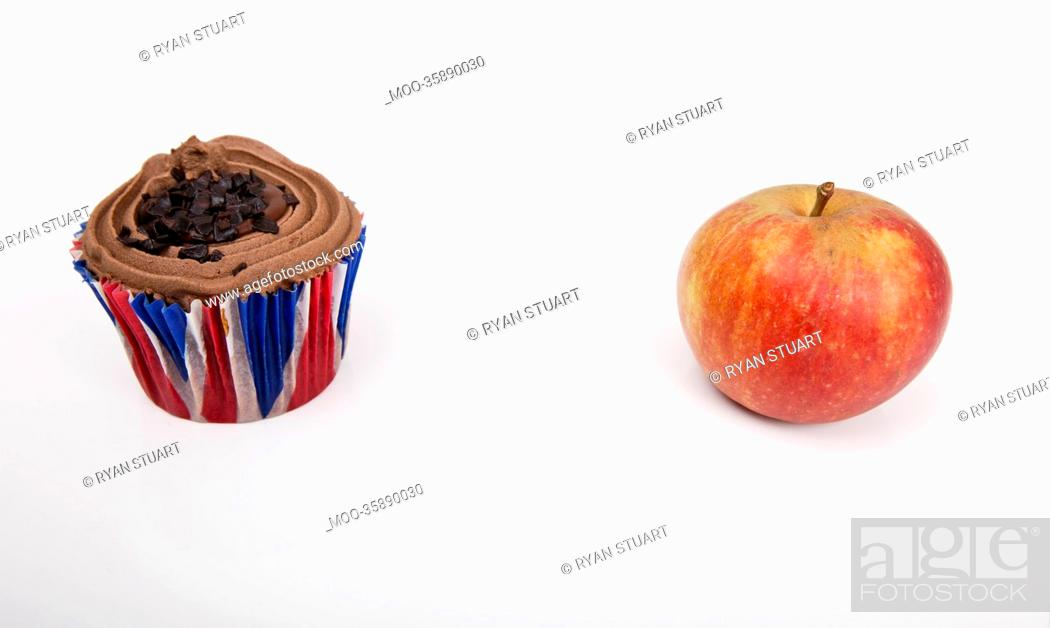 Stock Photo: Fresh apple and chocolate cupcake against white background.