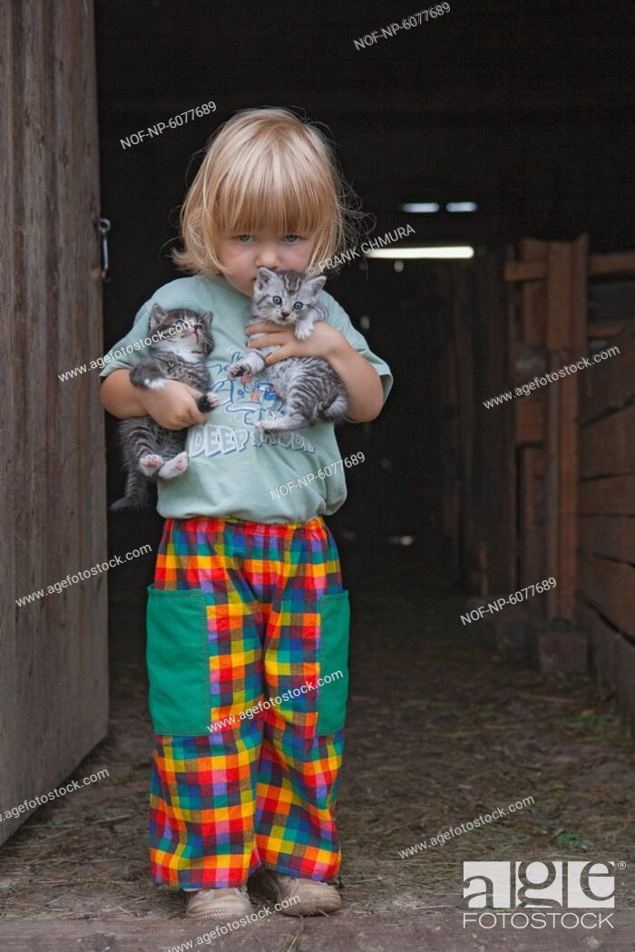 Stock Photo: Blond boy holding two kittens at the stable door.