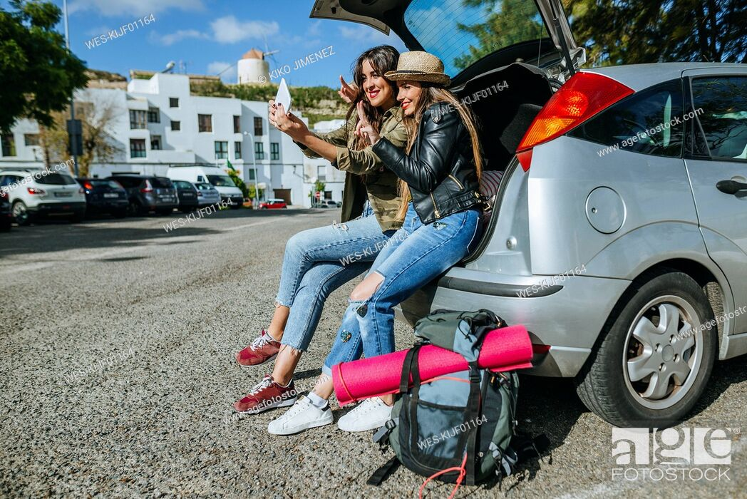 Stock Photo: Young women taking a selfie sitting in the trunk of a car.