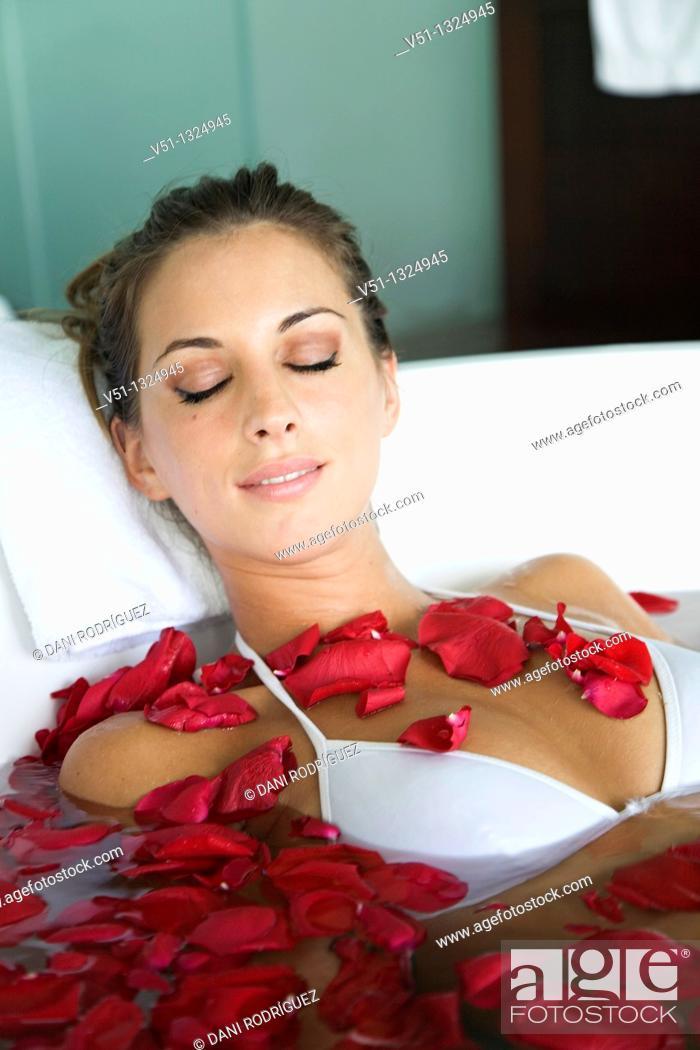 Stock Photo: Woman enjoying a bath with petals.