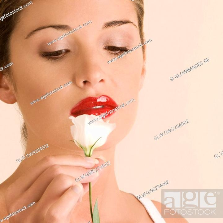 Stock Photo: Close-up of a young woman looking at a white rose.