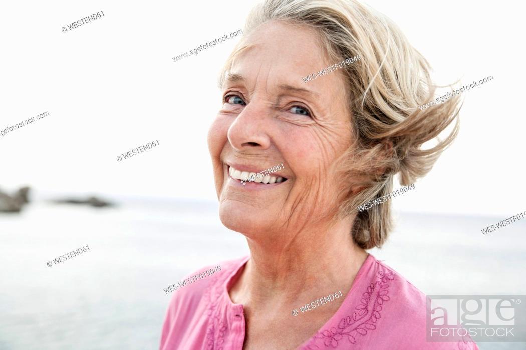 Stock Photo: Spain, Senior woman smiling at Atlantic ocean.