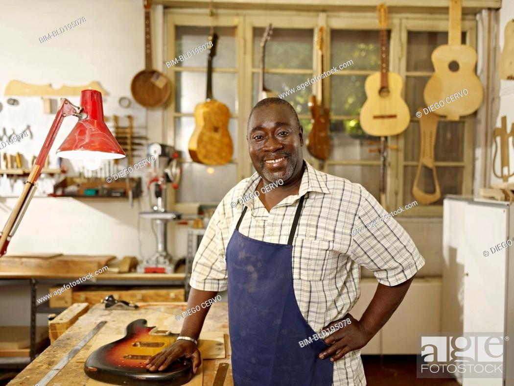 Imagen: Black craftsman in guitar workshop.