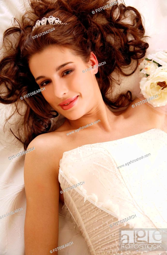 Stock Photo: Bride lying down on wedding bed.