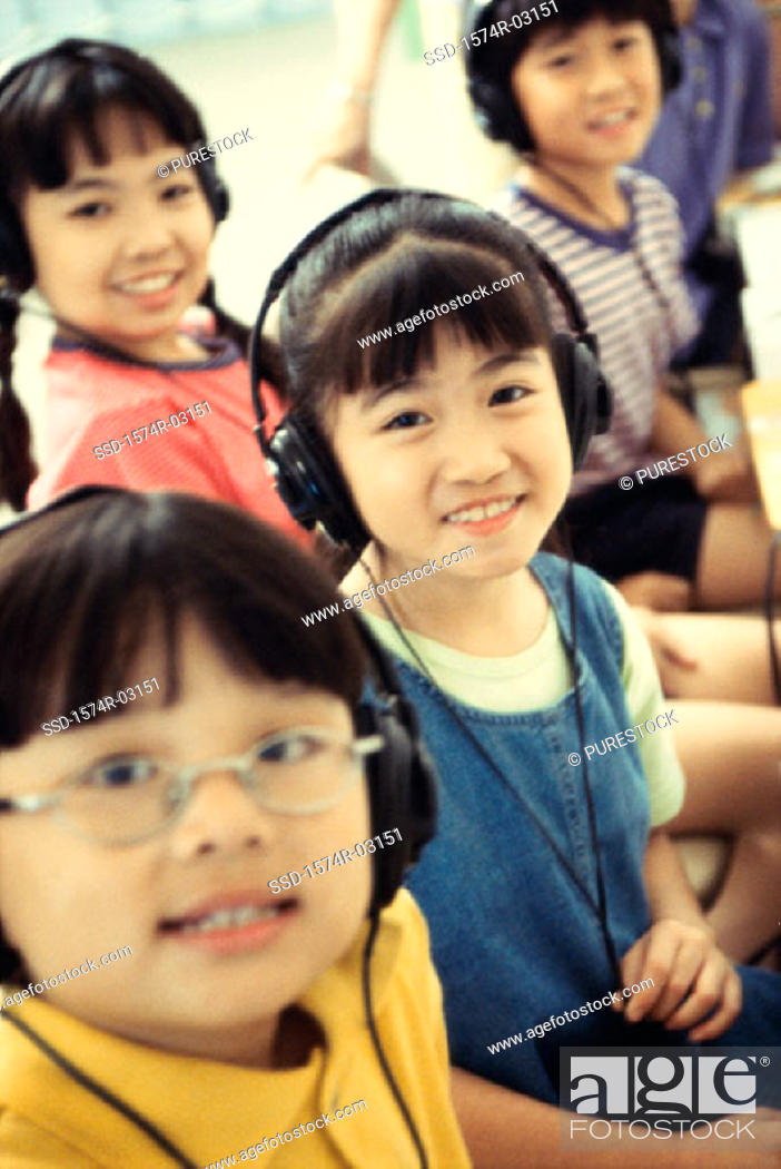 Stock Photo: Portrait of a group of children wearing headphones smiling.