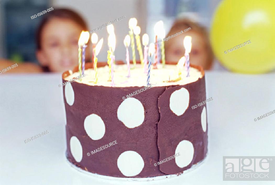 Stock Photo: Children looking at birthday cake.