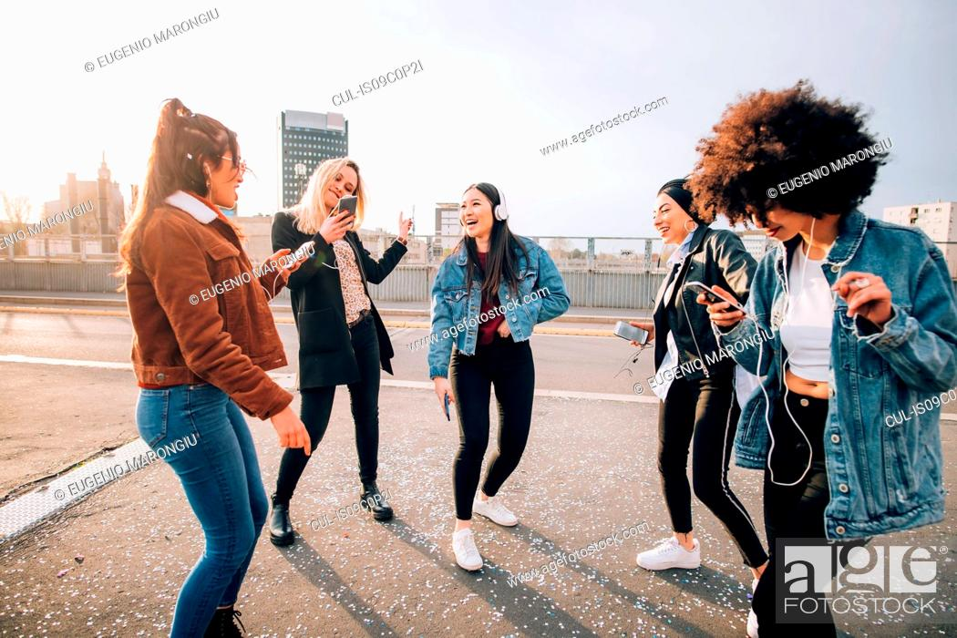 Stock Photo: Friends dancing in street to smartphone music, Milan, Italy.