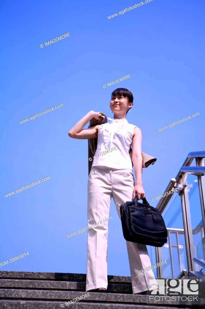 Stock Photo: Young woman standing on a staircase, holding briefcase and looking up with smile.