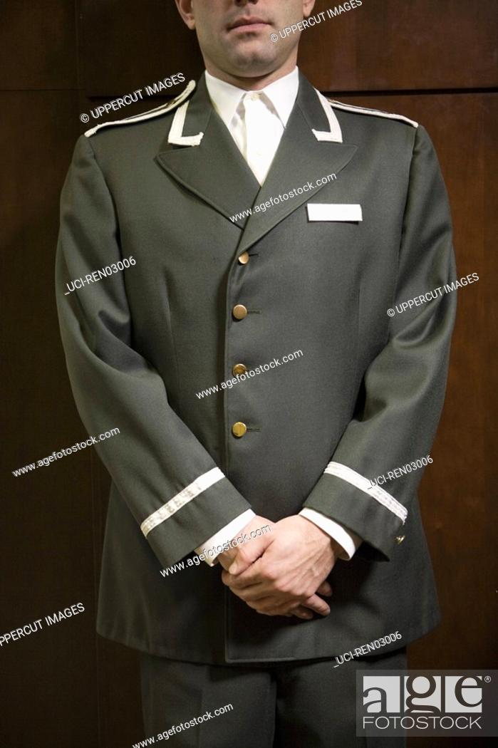 Stock Photo: Bellhop with hands clasped.