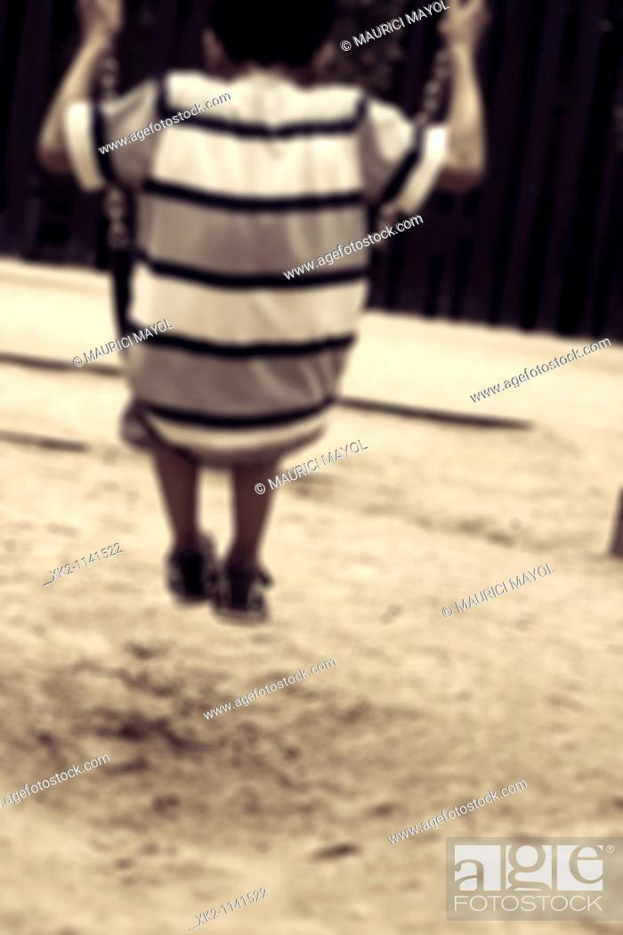 Stock Photo: niño de espaldas columpiándose en el columpio del parque infantil. Imagen de nostalgia.