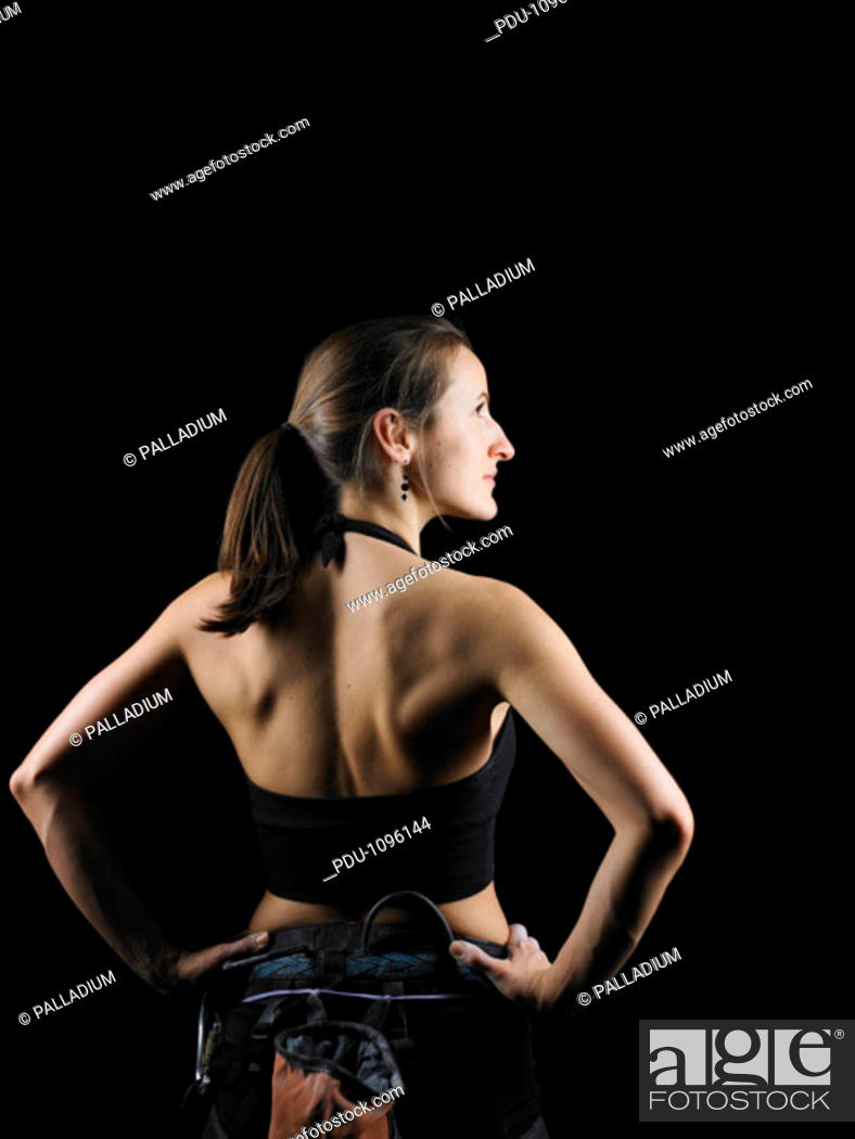 Stock Photo: Young female rock climber wearing harness, hands on hips, rear view.