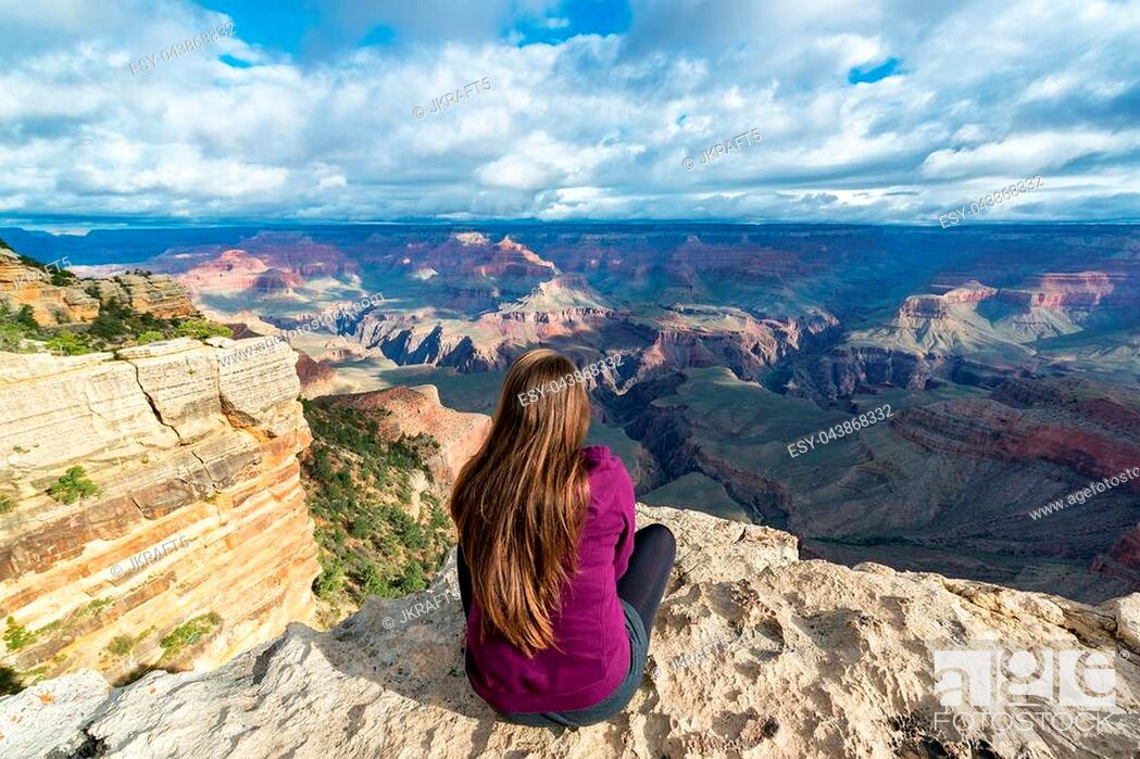 Stock Photo: Beautiful woman looking out at the Grand Canyon from the South Rim.