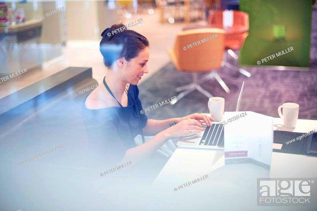 Stock Photo: Businesswoman sitting in airport lounge, using laptop, smiling.