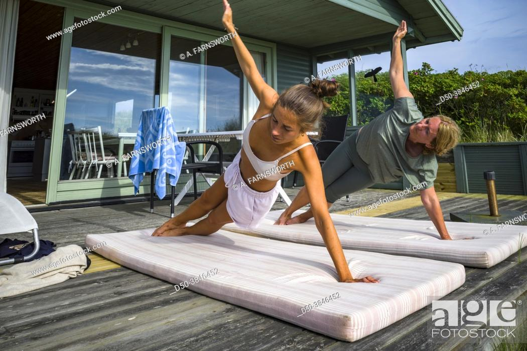 Stock Photo: A mother and daughter do yoga together.