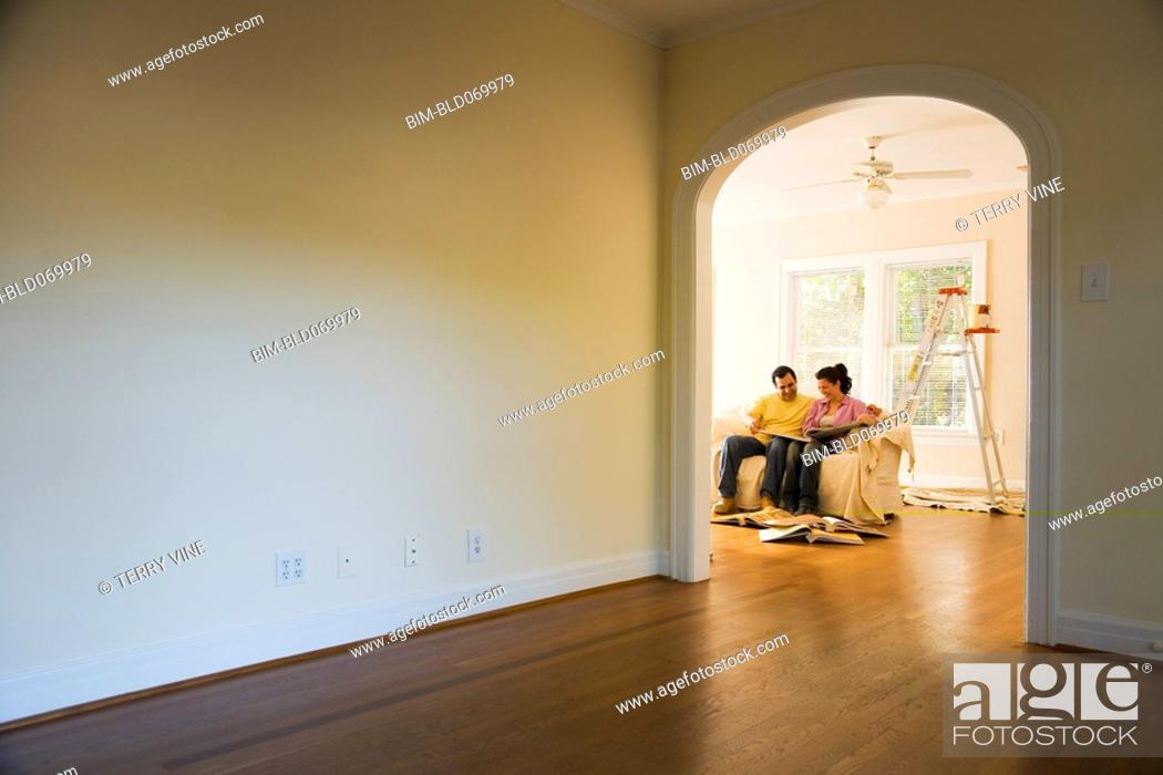 Stock Photo: Hispanic couple with painting supplies in new home.